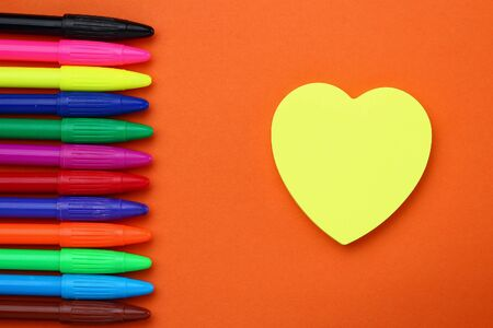 Heart-shaped sticker and multicolored felt-tip pens. Space for inscription or text.