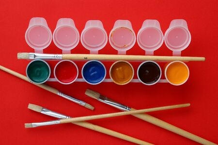 Flat art brushes for writing text or drawing and jars with multi-colored paints. The concept of analog creativity