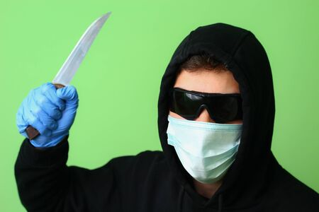 Young male gangster or criminal in a medical surgical mask and sunglasses dressed in black clothes with a hood holds a knife in his hand