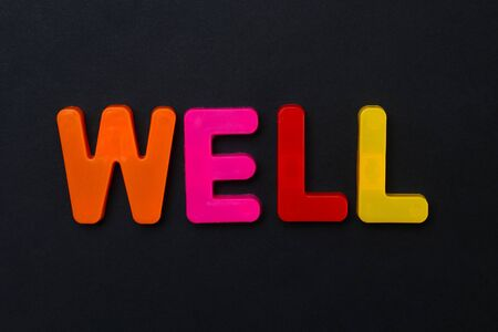 The word WELL written in letters of the children's magnetic alphabet on a black background