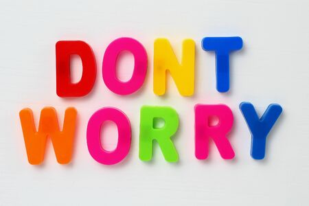 Text DONT WORRY made by magnetic letters on a white wooden background. Business Success Motivation