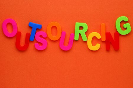 Text made in multicolored magnetic letters. OUTSOURCING. Color paper background