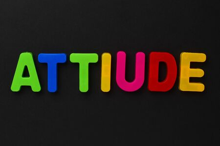 Text made in multicolored magnetic letters. ATTIUDE. Black background