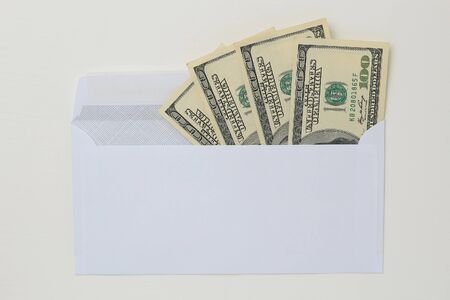 Classic white new mail envelope with dollars inside on a white wooden background. Copy space for text or lettering.