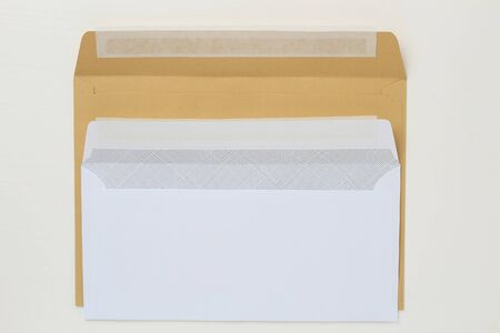 Two classic paper envelope on a white wooden table. Blank space for text