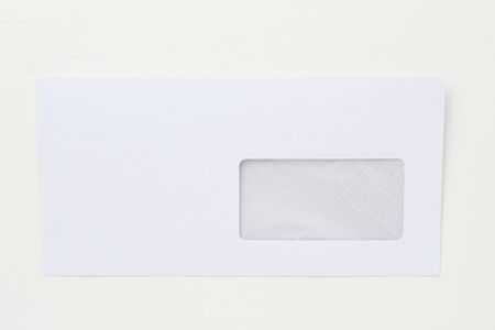 Classic postal paper envelope on a white wooden table. Blank space for text