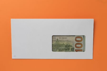 Classic white new mail envelope with dollars inside on an orange background. Copy space for text or lettering.
