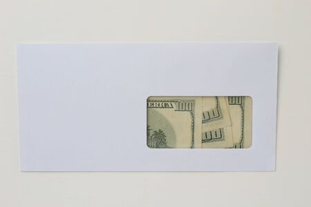 Classic white new mail envelope with dollars inside on a white wooden background. Copy space for text