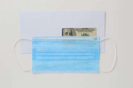 Classic white new mail envelope with dollars inside and a medical surgical mask on a white wooden background