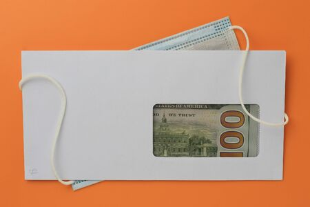 Classic white new mail envelope with dollars inside and a medical surgical mask on an orange background. Copy space for text or lettering.