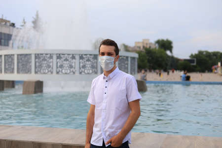 Lifestyle portrait of a young Caucasian man in a medical surgical mask protecting his face on a blurred background of the urban environment