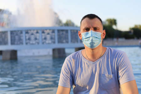 Happy smiling young tourist guy dressed in casual clothes and a medical surgical mask protecting his face during the covid-19 pandemic.