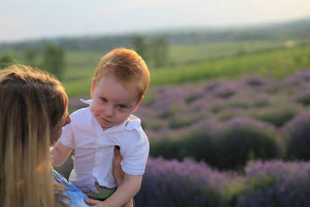 Lifestyle photo shoot of a real family in nature. Mom and son enjoy a stroll through the fresh air and scent on a lavender field in the rays of the setting sun. Selective focus.