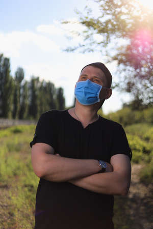 Caucasian young man or adult guy in casual clothes and medical surgical mask enjoys nature outside the city. Toned background