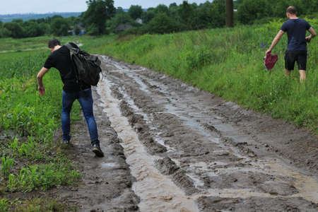 Tourists outside the city fell in heavy rain and walk along a soggy dirt road towards civilization.