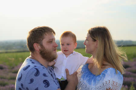 Lifestyle photo shoot of a real family in nature. Mom, dad and son enjoy a walk through the fresh air and the scent on the lavender field in the rays of the setting sun. Selective focus.