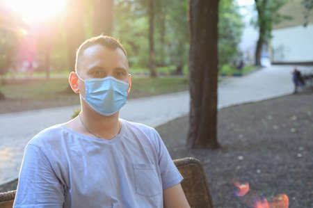 Caucasian young man or adult guy in casual clothes and a medical surgical mask is resting in a city park.