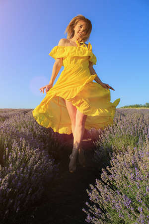 Happy young pretty woman jumps from happiness at sunset in a lavender field. The concept of freedom and positive. Toned background. Lifestyle emotions Foto de archivo