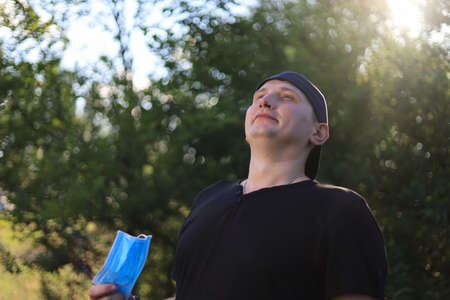 A white young man or adult guy in casual clothes is happy to breathe full chest by taking off his medical protective mask in a city park. Toned background