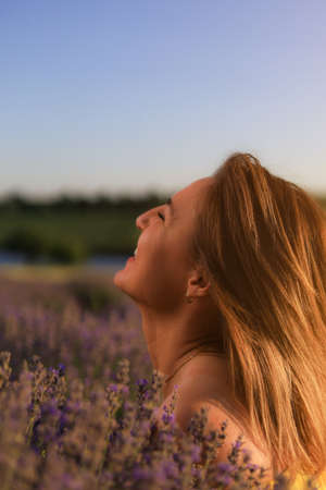 Happy young pretty woman in profile enjoys the smell of flowers and solitude with nature at sunset in a lavender field. The concept of freedom and happiness. Toned background