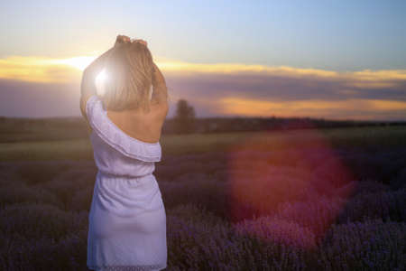 Silhouette of a woman in a white dress on a blurred background of a lavender field during sunset. The view from the back. Toned background with copyspace.