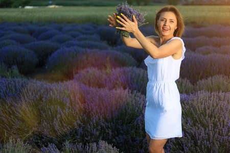 Happy young pretty woman walks at sunset in a lavender field with a bouquet in her hands and enjoys solitude with nature. Concept of freedom and happiness. Toned background with copyspace
