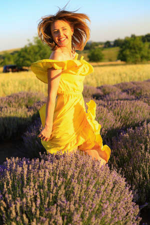 Happy young pretty smiling woman in a yellow dress dancing with happiness at sunset in a lavender field. The concept of joy and positive. Toned background. Lifestyle emotions Foto de archivo