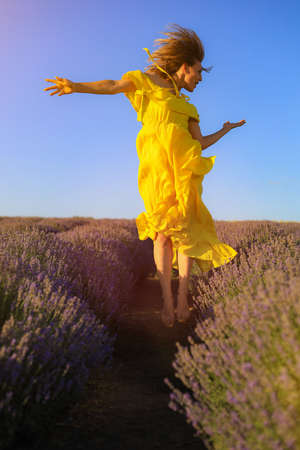 Happy young pretty woman jumps from happiness at sunset in a lavender field. The concept of freedom and positive. Toned background. Lifestyle emotions