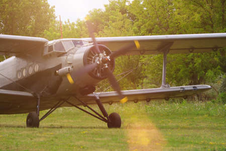 Classic old retro vintage airplane with a propeller at a green airfield.