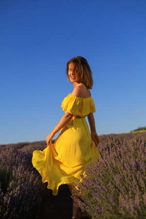 Happy young pretty modest smiling woman enjoying fresh air and aroma at sunset in a lavender field. The concept of freedom and unity with nature. Toned background. Lifestyle emotions