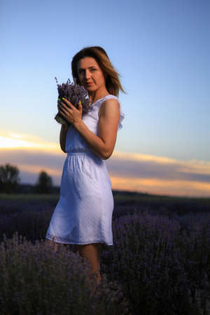 Happy young pretty woman walks at sunset in a lavender field and enjoys the smell of flowers and solitude with nature. The concept of freedom and happiness. Toned background