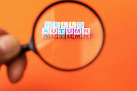 Text or inscription hello autumn. Cubes with letters under a magnifying glass on an orange background with copyspace.