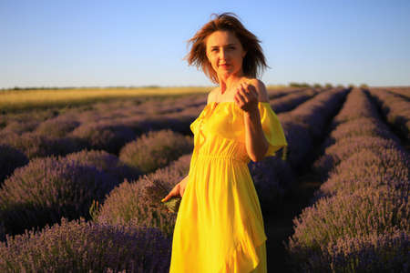 Happy young pretty woman walks at sunset in a lavender field with a bouquet in her hands and enjoys solitude with nature. Concept of freedom and happiness. Toned background