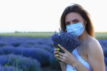 White Caucasian young woman or adult girl in a medical surgical mask with a bouquet of lavender in the field. Lifestyle portrait with copyspace Foto de archivo