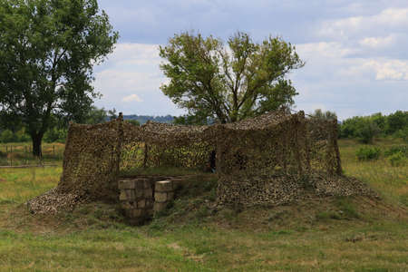 Military camouflaged dugout leading to an underground bunker.