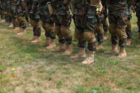 Legs of real soldiers in military boots and clothes standing in formation on the grass. Background with copyspace. Фото со стока