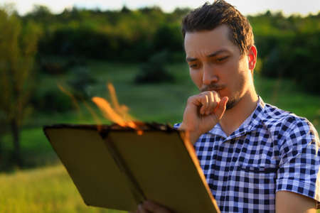 White Caucasian young man or adult guy reading a burning book on blurred forest background. Serious thoughtful face.