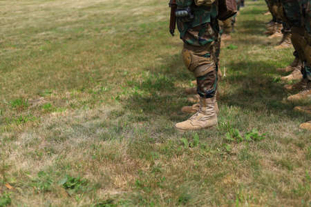 Legs of real soldiers in military boots and clothes standing in formation on the grass. Background with copyspace.