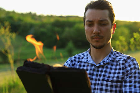 White Caucasian young man or adult guy reading a burning book on blurred forest background.