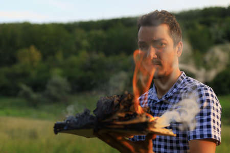 White Caucasian young man or adult guy holds in hands a burning book on blurred forest background.