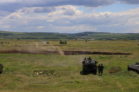 Armored personnel carrier infantry fighting vehicle. Military background with copyspace. Heavy armored military police truck in a green field. Imagens