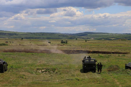 Armored personnel carrier infantry fighting vehicle. Military background with copyspace. Heavy armored military police truck in a green field. Banque d'images