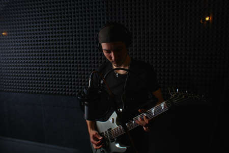 Young handsome creative man with a guitar in the darkness of a music studio, toned background
