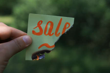 Burnt sticker with word sale on blurred background