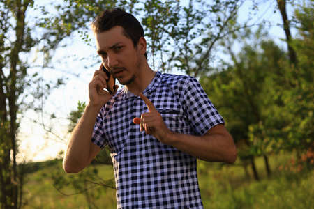 Young white Caucasian man, freelancer with the phone tensely solves business issues while in nature outside the city. Lifestyle Foto de archivo