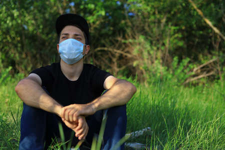 Young white Caucasian man in protective mask on blurred green forest background. Foto de archivo
