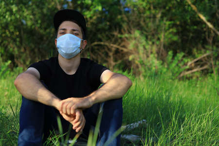 Young white Caucasian man in protective mask on blurred green forest background. Foto de archivo - 153589218