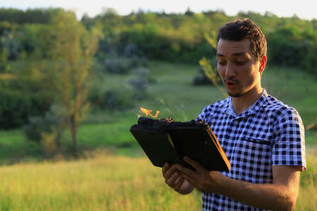 White Caucasian young man or adult guy reading a burning book on blurred forest background. Foto de archivo - 153589473