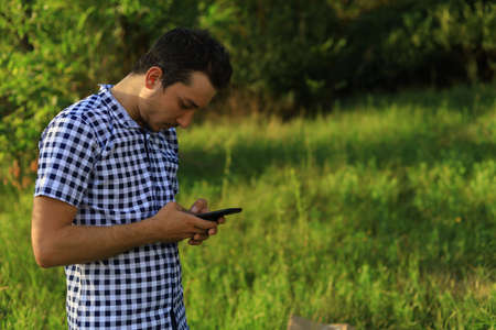 Young white Caucasian man, freelancer with the phone tensely solves business issues while in nature outside the city. Lifestyle Foto de archivo - 153527335