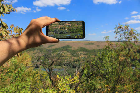 A tourist takes photographs with his phone of a view of the river from a huge hill or mountain on a hike. Green forest nature background. Selective focus. Foto de archivo - 153589479